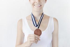 mulher segurando a medalha de bronze foto