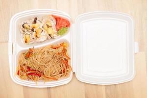 macarrão chinês e rolos japoneses na caixa foto