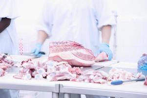 açougueiro que corta carne de porco fresca foto