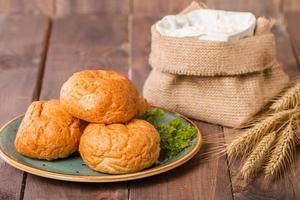 pães no prato e espigas de centeio e farinha foto