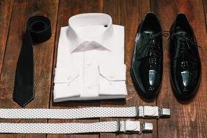 gravata preta, sapatos de couro, suspensórios, camisa branca