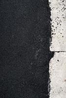 novo concreto de asfalto perto da calçada de concreto foto