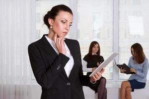 mulher com roupas formais lê pensativamente as informações do foto
