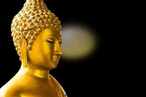 Buda de ouro isolado no fundo preto foto