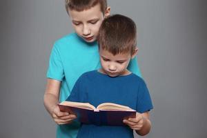 garotinhos lendo livro interessante foto