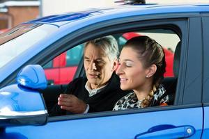 jovem mulher recebendo instruções de seu instrutor de condução foto