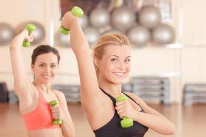 par de mulheres fazendo pesos fitness foto