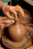 mãos do oleiro, criando um pote de barro foto