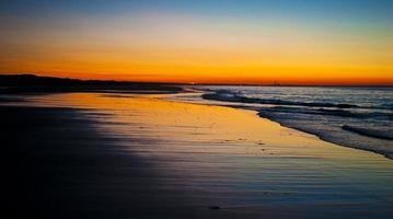 pôr do sol na praia de areia no pescoço
