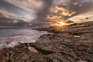 pôr do sol nas rochas da ilha de karpathos.