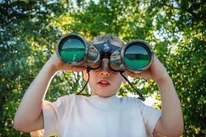 menino olhando através de binóculos