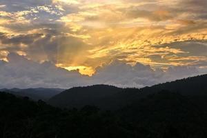 sol brilhando através da nuvem sobre a montanha foto