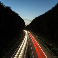 trilhas leves de carro na estrada ao pôr do sol foto