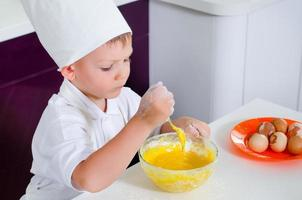 bonito rapaz aprendendo a enfardar um bolo foto