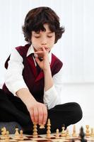 retrato de um menino de 8 anos jogando jogo de xadrez foto