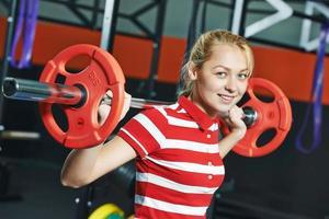 mulher com barra de peso no ginásio de fitness foto