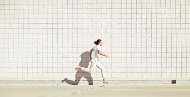 corredor livre descalço (atleta de parkour) vestido todo de branco foto
