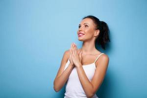 mulher jovem e atraente está rezando para dar boa sorte