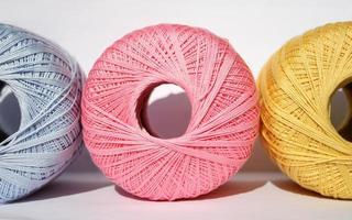 três bolas de fio colorido