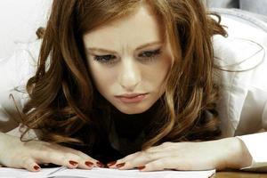 estudante preocupado olhando livro foto