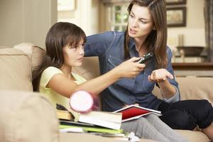 mãe fica frustrada enquanto a filha assiste tv foto