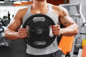 powerlifter com disco de peso nas mãos foto