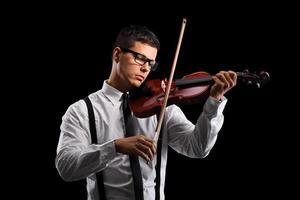 jovem violinista masculina tocando um violino acústico foto