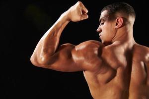 fisiculturista masculina flexionando os bíceps, vista traseira com espaço de cópia