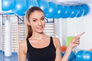 mulher jovem e bonita no ginásio. ela está apontando o espaço da cópia foto