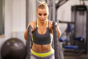 jovem mulher malhando com cordas de batalha em uma academia foto