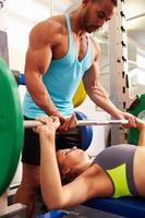 mulher levantando pesos com a ajuda do treinador, vista lateral foto