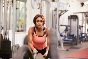 jovem mulher malhando com cordas de batalha em uma academia