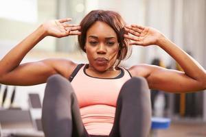 jovem mulher fazendo abdominais em uma academia, close-up foto