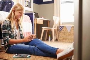 menina usando telefone inteligente no quarto dela