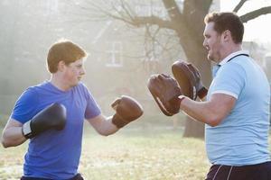 treinamento de boxeador com treinador ao ar livre foto
