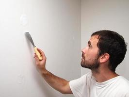 homem cobrindo buracos com um cimento. foto