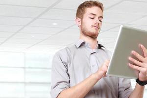 empresário bonito usando o tablet pc foto
