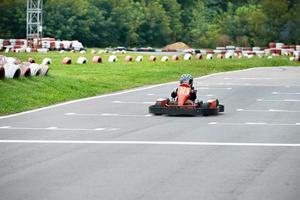 pequeno piloto de kart na pista foto