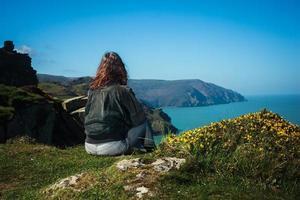 jovem mulher sentada na beira do precipício