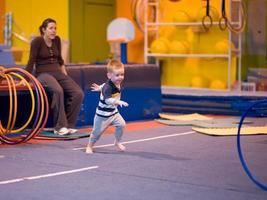 menino perseguindo um aro no ginásio foto