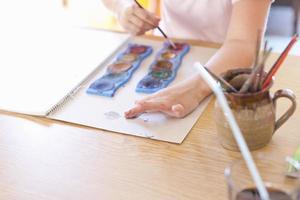 menina pintura a dedo com aquarelas