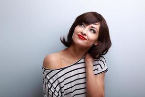 mulher feliz cabelo curto pensando e olhando para cima foto