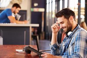 homem usando tablet digital em uma cafeteria foto