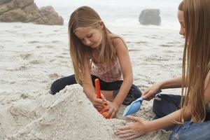 irmãs fazendo castelo de areia na praia foto