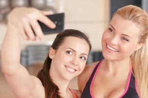 par de garotas fazendo selfie no ginásio foto