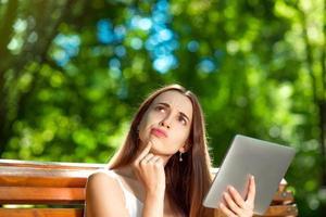 jovem mulher com tablet digital no parque