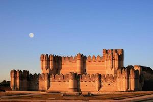 a fortaleza da coca (Espanha) ao entardecer com lua cheia foto