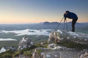 fotógrafo no topo da montanha ao pôr do sol