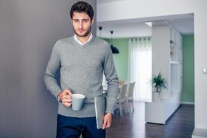bonito jovem empresário sorridente, trabalhando em casa foto