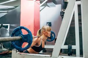 mulher de fitness fazendo agachamento em um ginásio foto